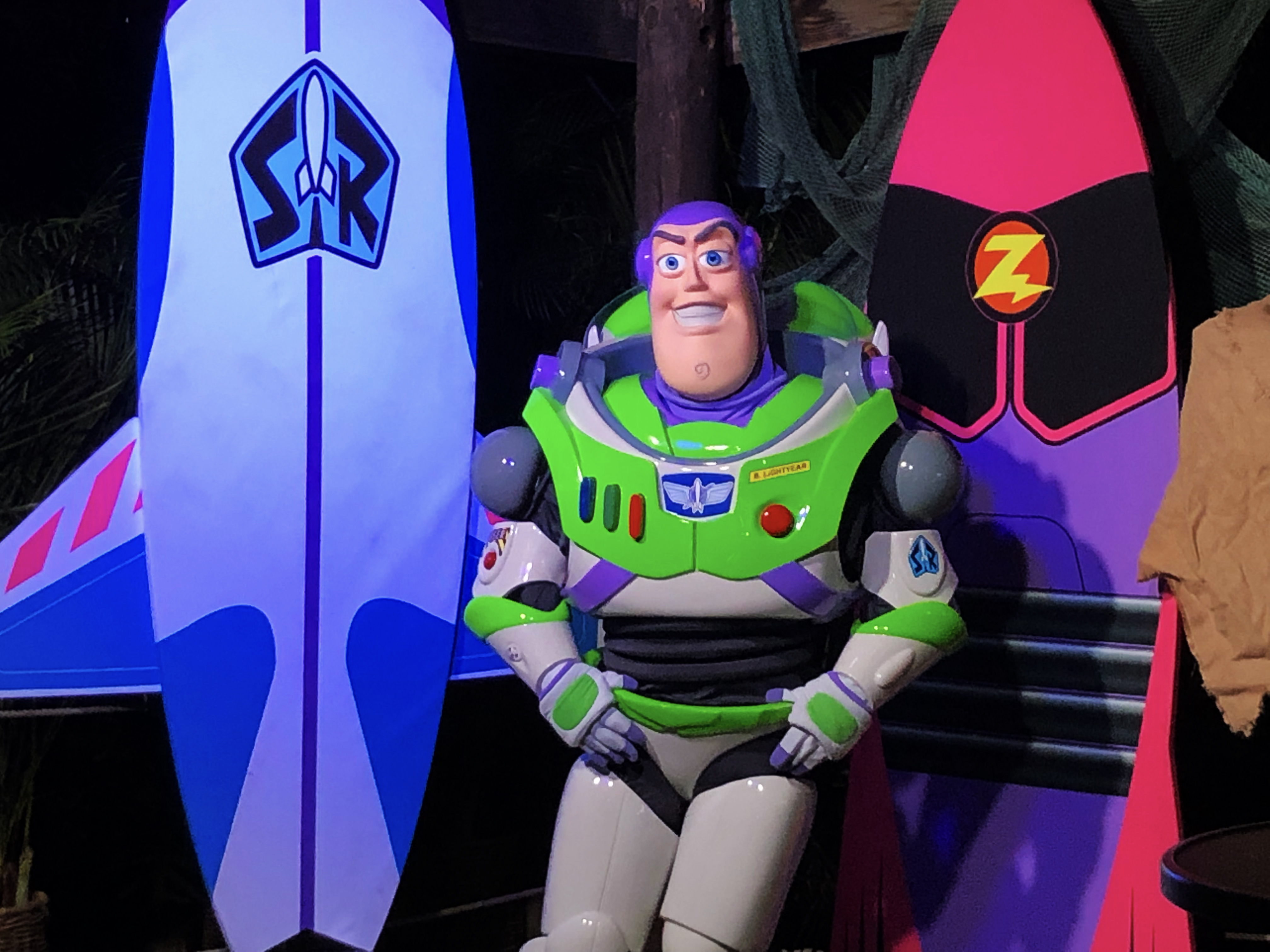 Toy Story character, Buzz Lightyear, stands with his hands on his waist while in front of Star Command and Zurg-inspired surfboards. He waits for the next guest for a meet and greet photo session during night at Disney's Typhoon Lagoon.