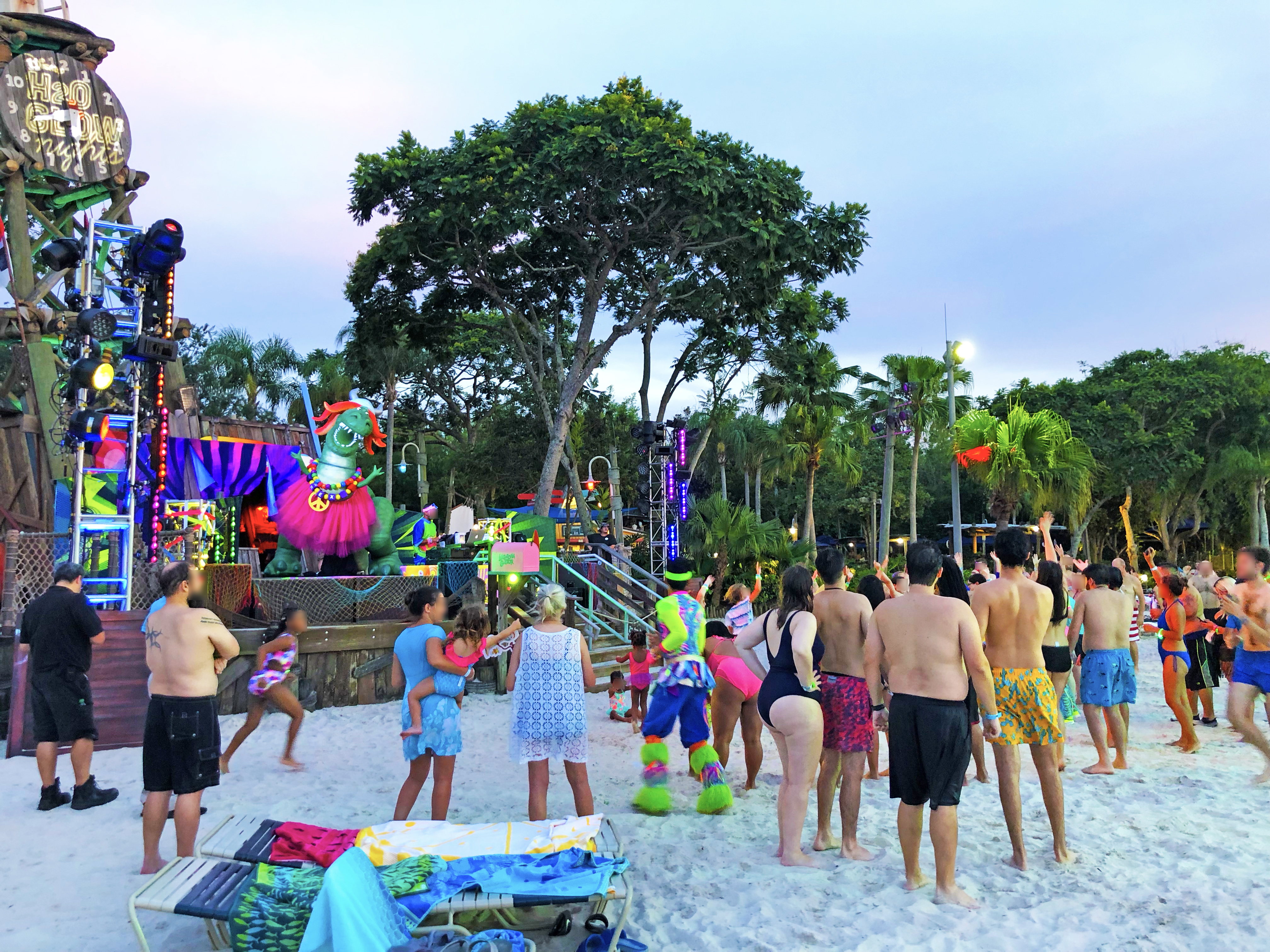 Crowd of people standing, running and/or dancing on the beach sand as a DJ is on a lit-up live stage in front of Disney's Typhoon Lagoon clock tower (which reads Disney's H2O Glow Nights). During the daytime. On stage, Toy Story character, Rex, is posed with his arms up in the air while wearing a pink tutu, some necklaces, and an orange wig and a silver horn metal helmet.