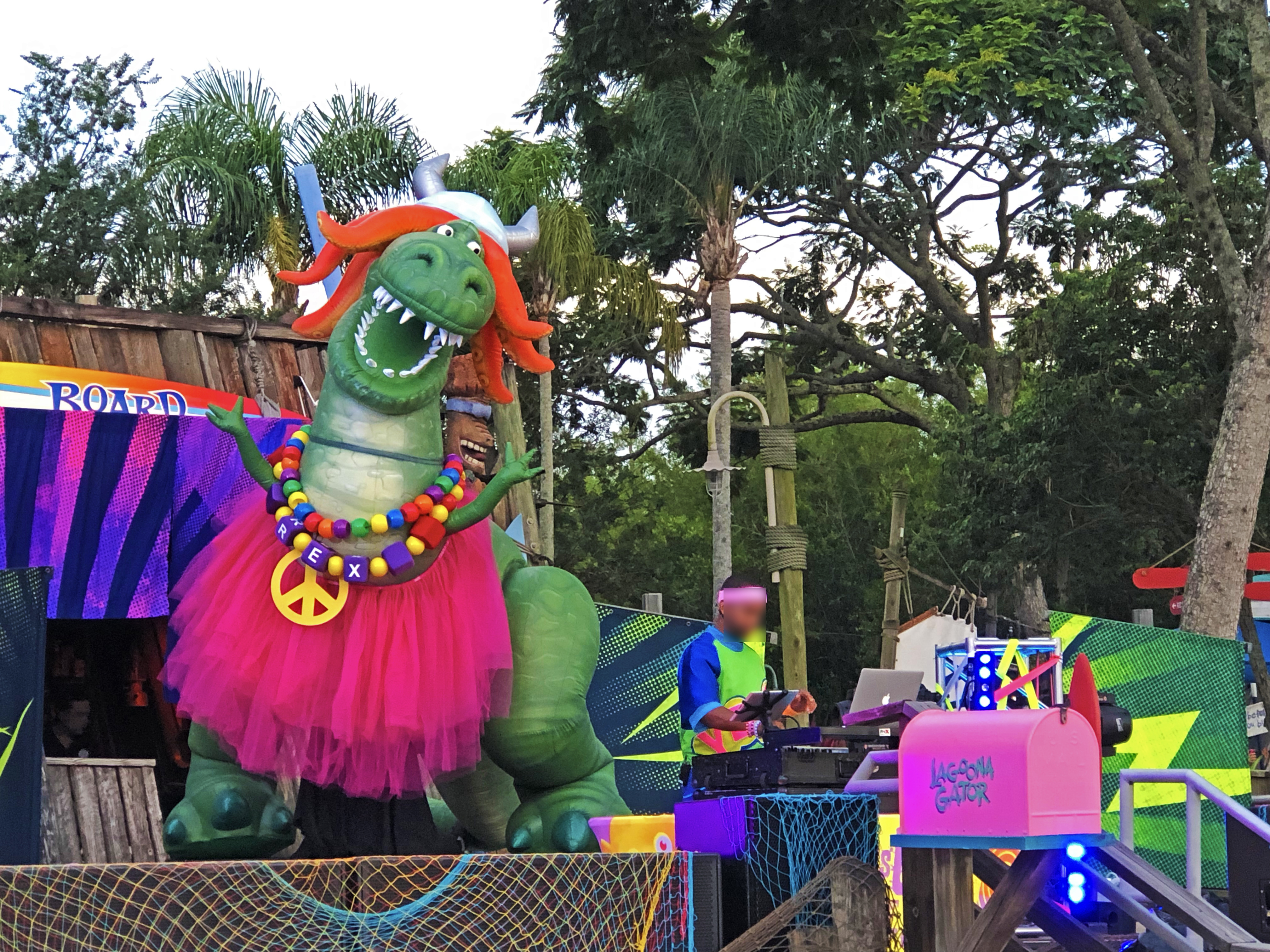 On stage, Toy Story character, Rex, is posed with his arms up in the air while wearing a pink tutu, some necklaces, and an orange wig and a silver horn metal helmet of sorts. During the daytime at Disney's Typhoon Lagoon for Disney's H2O Glow Nights.