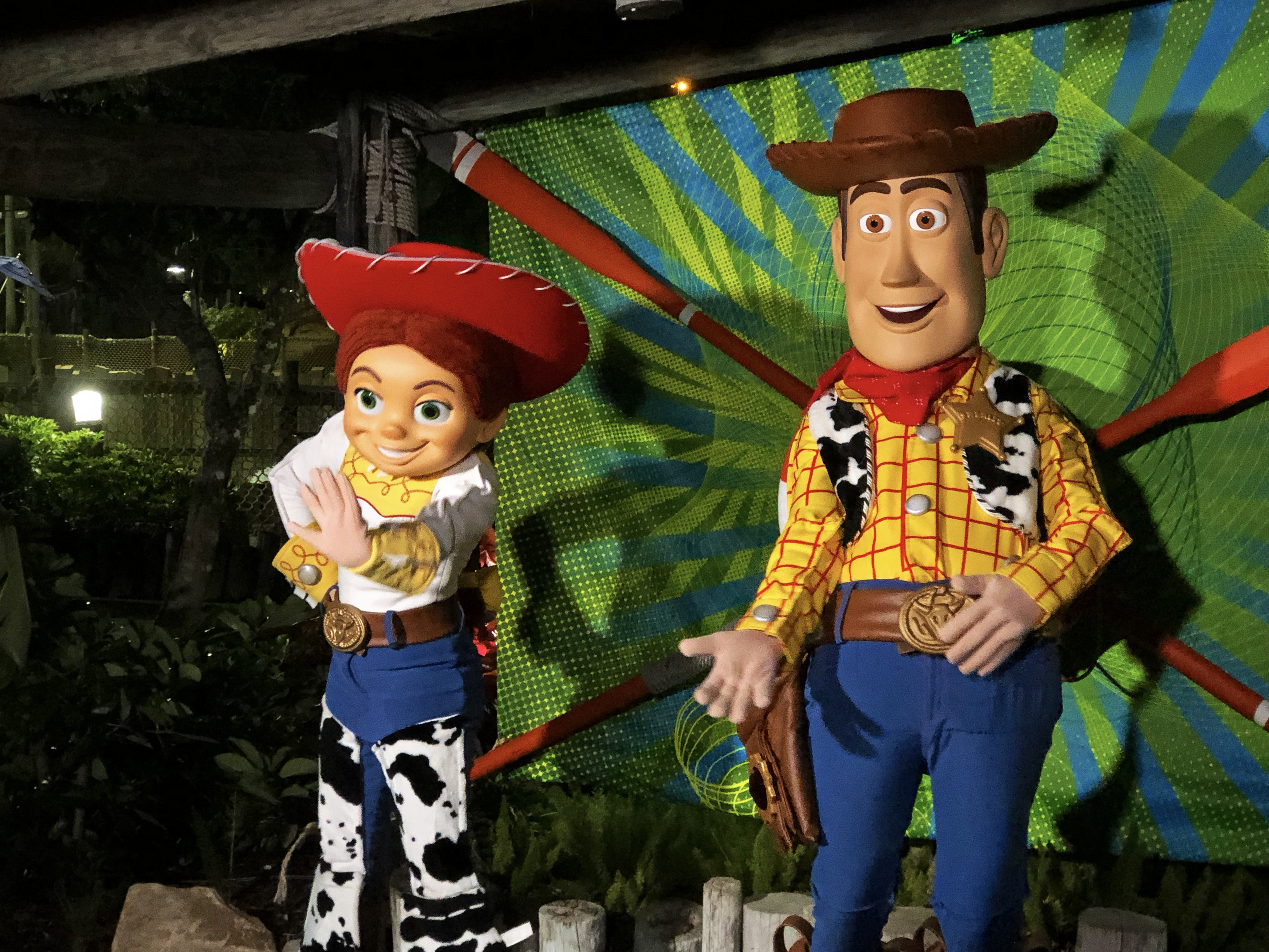 Toy Story characters, Jessie (waving) and Woody (with his hand out) stand in front of green, blue and orange background to get ready for photos with guests during night at Disney's Typhoon Lagoon.