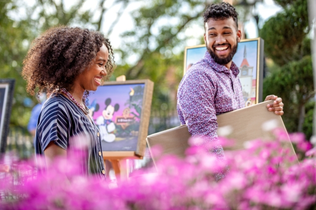 Woman, left, and man, right, walking and laughing at Epcot® International Festival of the Arts. Man is carrying wrapped painting.