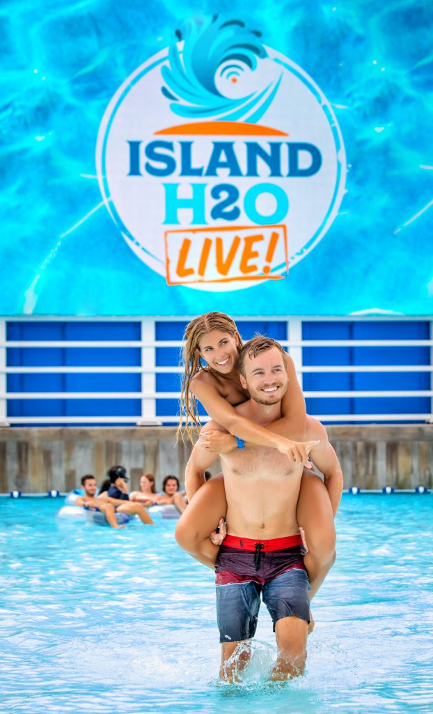 Woman piggybacking on man in wave pool in front of Island H2O Live! wave pool tc screen