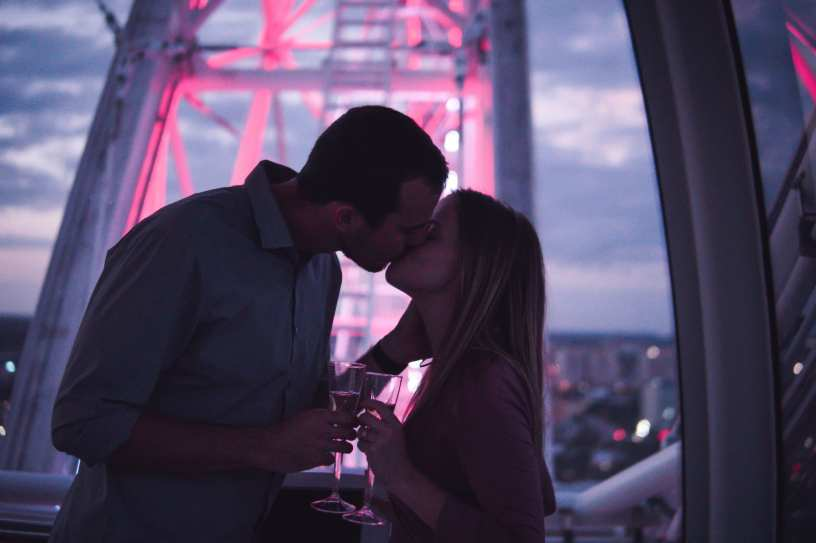 Late afternoon post-sunset photo of couple kissing on The Wheel at ICON Park